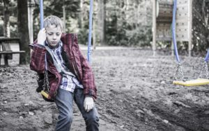 Sad or depressed boy sitting in playground swing